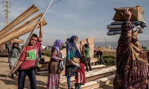 Syrian refugees at an informal settlement in Lebanon carry aid items, including wood to strengthen their shelters for winter.