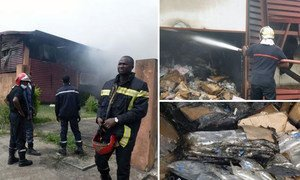 Emergency personnel try to contain a fire on 18 December 2014 at a warehouse at the main humanitarian logistics base in Conakry, Guinea, which contained critical Ebola response supplies.