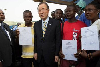 Secretary-General Ban Ki-moon (centre) stands with Ebola survivors in Sierra Leone, seen here showing their hospital discharge certificates.