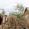 A displaced Somali woman stands at the entrance to her temporary home at the Ifo 2 Refugee Camp in Dadaab, Kenya.