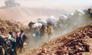 Syrian refugees arrive across the border into Jordan.