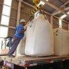 Des travailleurs chargent de la canne à sucre dans une distillerie d'éthanol au Brésil.