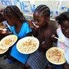 En Haïti, des enfants dans le bidonville de Port-au-Prince de Bel Air profitent d'un repas. Photo : MINUSTAH