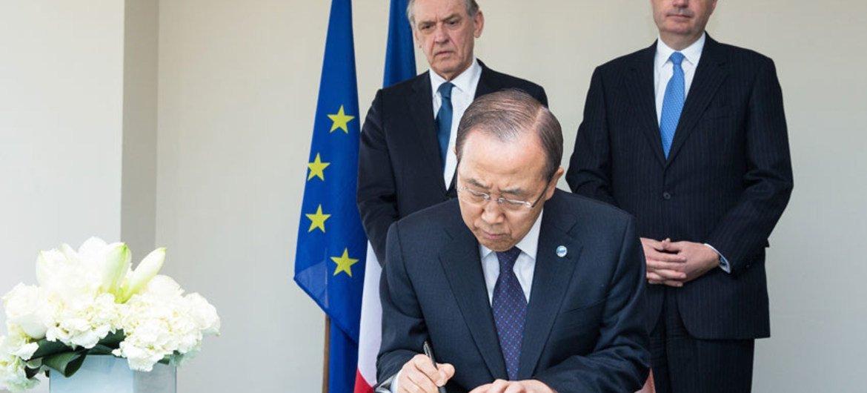 Le Secrétaire général de l'ONU, Ban Ki-moon, signe un livre de condoléances à la Mission permanente de la France auprès des Nations Unies. Photo : ONU/Evan Schneider