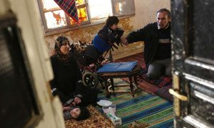 Members of a family gather on the floor of their dilapidated apartment in downtown Amman, Jordan.