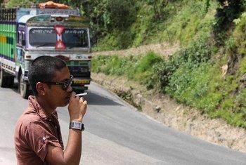 Un homme fume au bord de la route au passage d'un autobus au Népal.