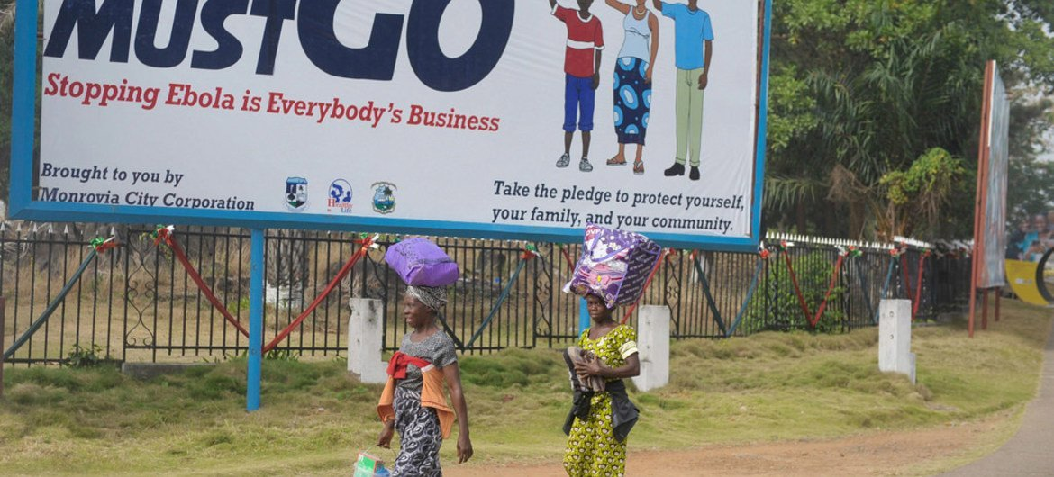 """Two women in Monrovia, Liberia, walk in front of a billboard, which says """"Ebola must go. Stopping Ebola is Everybody's Business."""""""