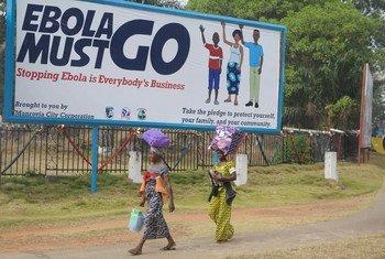"""Deux femmes à Monrovia, au Libéria, marchent devant un panneau d'affichage, qui dit """"En finir avec Ebola. Mettre fin à Ebola est l'affaire de tous"""". Photo : MINUL/Emmanuel Tobey"""