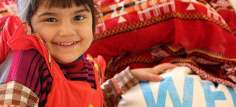 Una niña desplazada en Iraq, junto a una entrega de alimentos del PMA. Foto: PMA/Mohammed Al Bahbahani