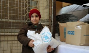 A child collects food from a WFP distribution centre in Syria.