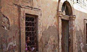 Une fille regarde à travers la fenêtre de sa maison à Benghazi, en Libye.