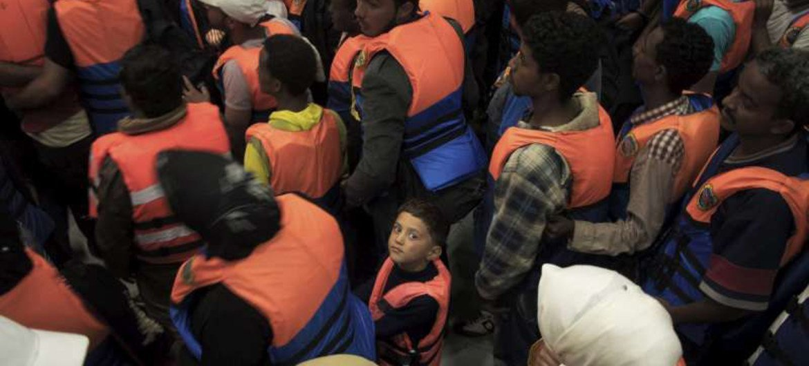 A young boy surrounded by adults after being rescued in June 2014 from a boat on the Mediterranean Sea.