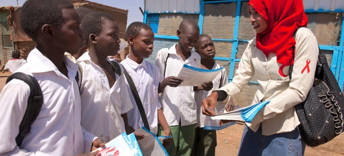 Peer educator Arafat speaks with a group of school children and distribute HIV/AIDS awareness materials, in a community in Khartoum, Sudan.