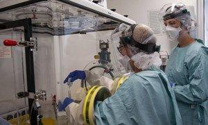 A team of lab technicians handle a sample for Ebola testing in a Laboratory in Sinje, Grand Cape Mount, Liberia.