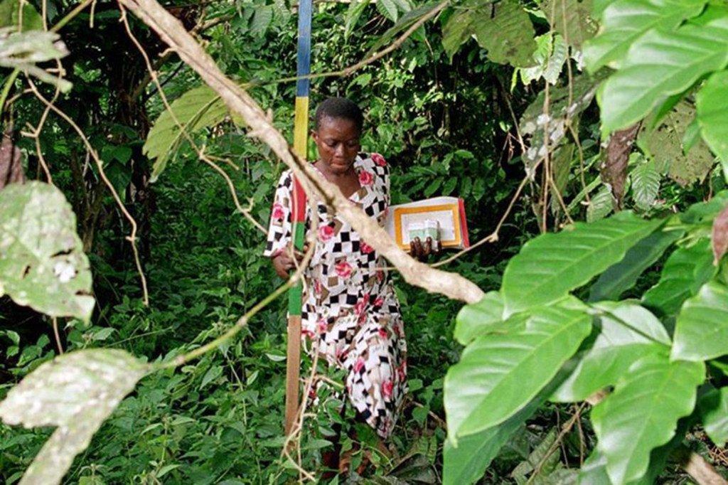 Msambazaji dawa kwenye jamii akiwa na kasha lake la dawa dhidi ya upofu kuelekea kijiji cha ndani zaidi huko Cameroon