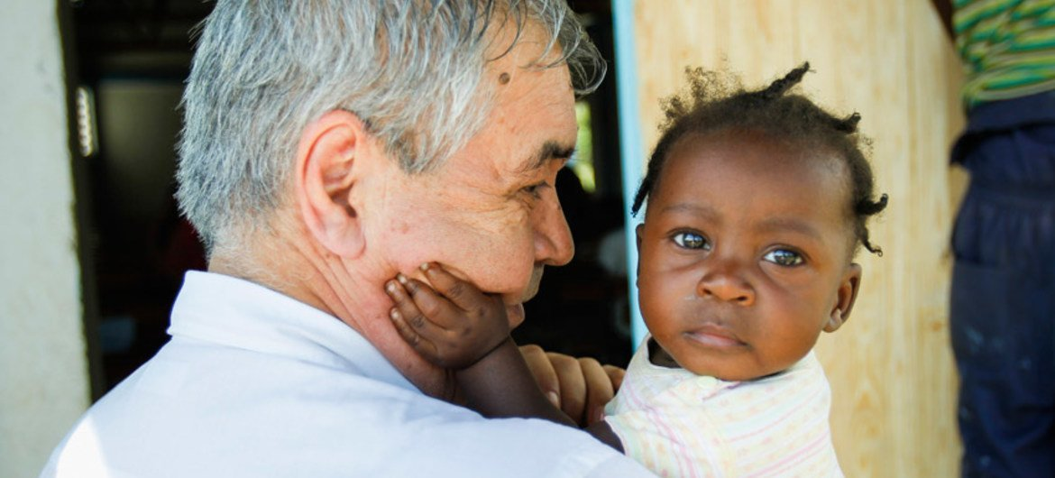 Pedro Medrano Rojas holds a child during a July 2014 visit to the community of Las Palmas, Haiti.