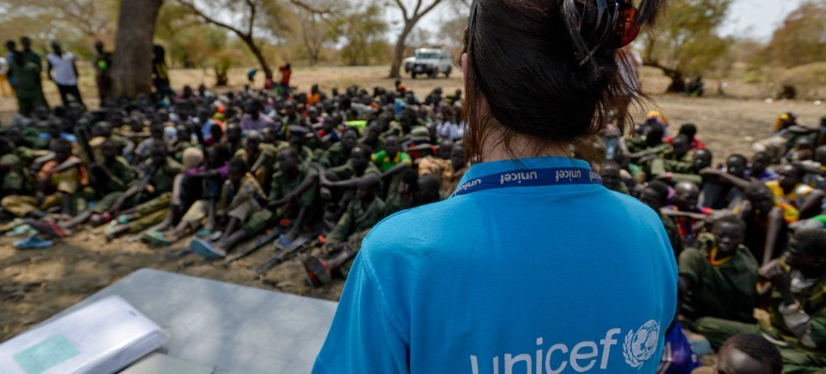A UNICEF worker stands in front of a group of children undergoing release from the SSDA Cobra Faction armed group, in Pibor, Jonglei State on 10 February 2015.