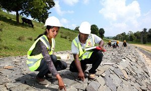 Working alongside her male team member, a woman employee checks the quality of work at a dam under construction in Sri Lanka.