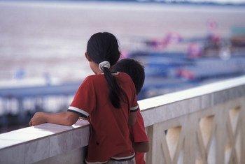 两名儿童站在老挝一个移民办公室的阳台上。联合国儿童基金会与老挝政府合作,以免这样的年幼儿童遭受贩运,被卖到国外从事危险的工作。儿基会图片 /LaoPDR04713/Jim Holmes