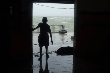 A child looks through a doorway as Cyclone Pam hits Vanuatu, March 2015.