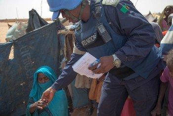 Un Casque bleu de la MINUAD discute avec une femme lors d'une patrouille au camp de déplacés de Zam Zam, au Nord-Darfour. Photo MINUAD/Hamid Abdulsalam