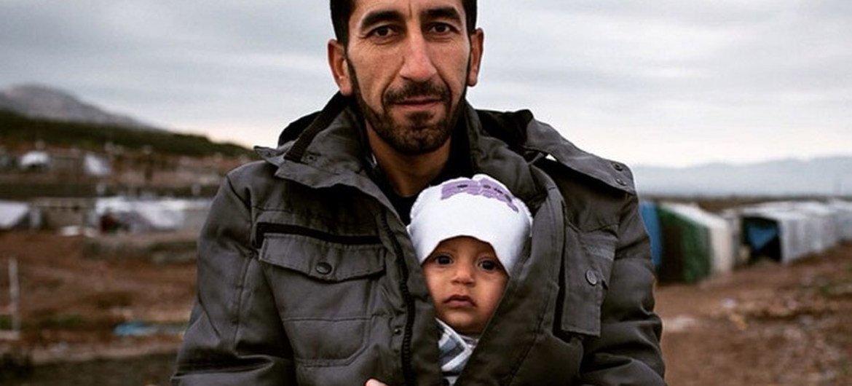Un réfugié syrien avec son fils dans un camp de réfugiés en Iraq. Photo : HCR/N. Colt