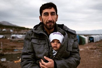 A Syrian refugee holds his baby son in a refugee camp in Iraq.