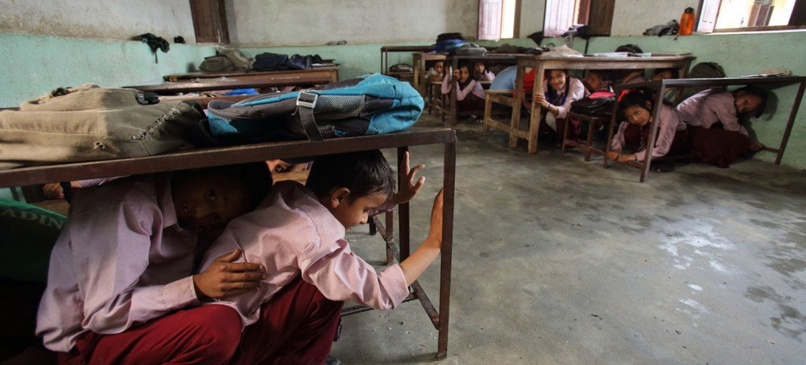 Students in Matatirtha, Nepal, which is in the process of being redeveloped to make the school more earthquake proof. As part of this process children are taught how to take shelter beneath their desks in case of an earthquake. Photo by Jim Holmes for AusAID.(13/2529)