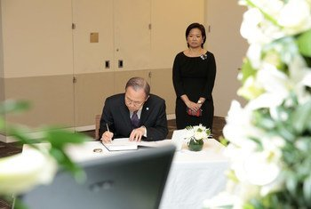 Secretary-General Ban Ki-moon signs a book of condolences on the passing of Lee Kuan Yew, the first Prime Minister of Singapore, at the country's Permanent Mission to the UN. Ambassador Karen Tan of Singapore looks on.
