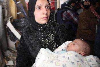 Mujer y niño palestinos en Yarmouk, un barrio de la capital siria.