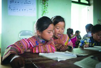 Two 5th graders do their assignment during class at PS La Pan Tan in Viet Nam.