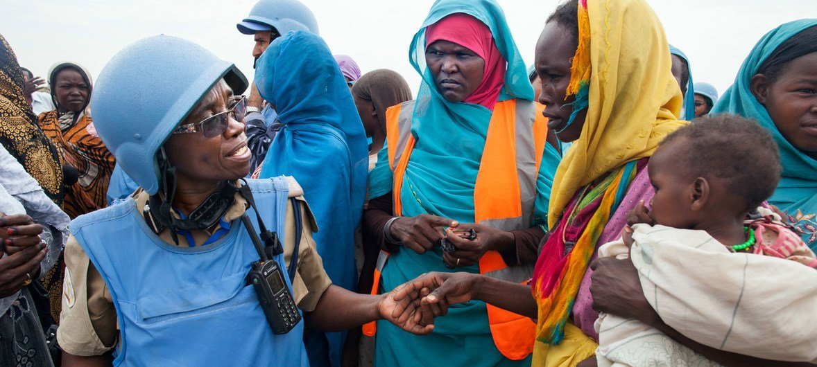 Tanzanian police officer Grace Ngassa (left), serving with the African Union-United Nations Hybrid Operation in Darfur (UNAMID), talks to a woman resident of Zam Zam camp for internally displaced persons (IDPs), near El Fasher, capital of North Darfur.