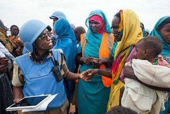 ضابطة الشرطة التنزانية غريس نغاسا (يسار)، التي تعمل مع بعثة يوناميد في دارفور، تتفاعل مع امرأة مقيمة في مخيم زمزم للنازحين، قرب الفاشر، عاصمة شمال دارفور.