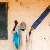 Aisha pretends to draw at the tip of a pencil painted on a wall mural in a camp for internally displaced people in Yola, the capital of Adamawa.