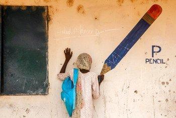 一位叫做艾莎的尼日利亚女孩儿在一座内部流离失所营地的墙上假装使用巨大的笔在作画。儿基会图片/Esiebo