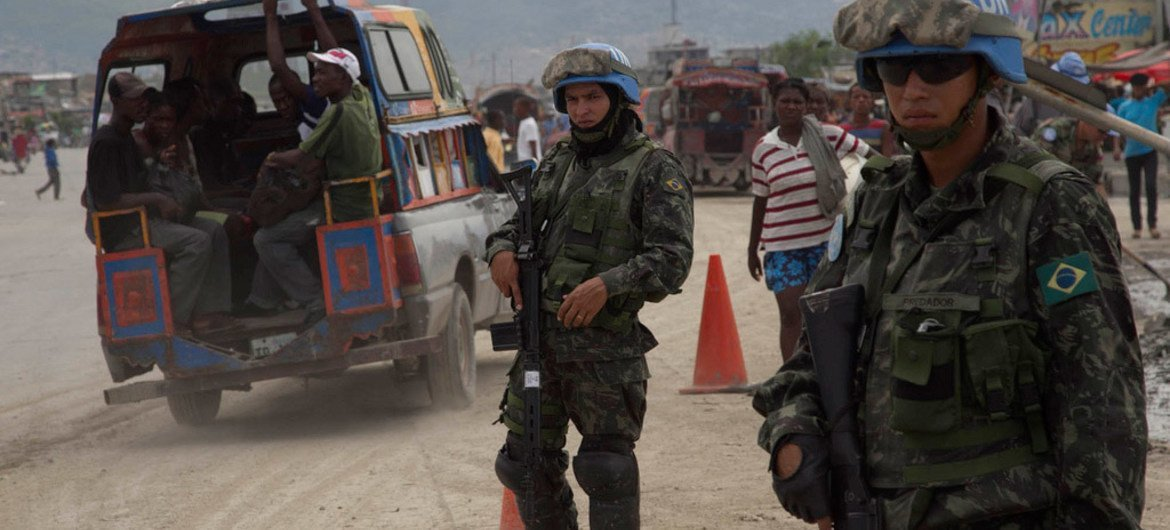 In Cité Soleil, Haiti, Chilean UN Peacekeeping Engineers carry out roadwork as Brazilian Peacekeepers provide security.