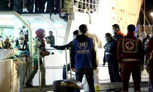 A UNHCR staff member watches as people rescued from the Mediterranean disembark from an Italian Coastguard vessel at Palermo, Sicily, on Tuesday 14 April 2015.
