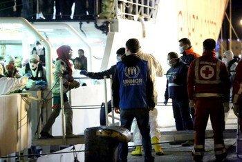 Un membre du personnel du HCR assiste au débarquement de migrants secourus en mer Méditerranée par un navire des garde-côtes italiens à Palerme, en Sicile, le mardi 14 avril 2015. Photo : UNHCR / F. Malavolta
