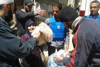 Сотрудники  БАПОР раздают  помощь  перемещенным  лицам   из лагеря  Ярмук в  Сирии.