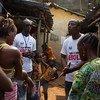 Movilizadores sociales acuden de puerta en puerta para hablar con los residentes de un barrio pobre en Freetown, la capital de Sierra Leona, sobre la lucha contra el ébola. Foto: UNICEF/Tanya Bindra.