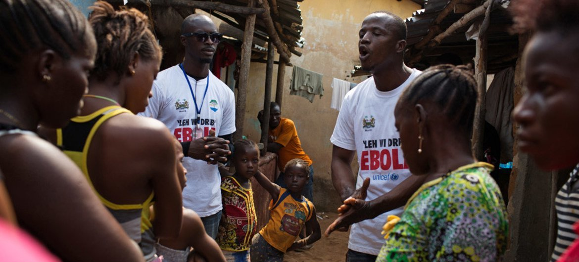 Social mobilizers going door-to-door, speak with residents of a slum in Freetown, the capital of Sierra Leone, in the fight against Ebola.