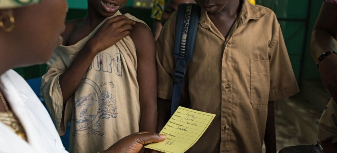 A nurse gives children their vaccination card after having received measles and polio vaccination, as well as deworming pills and Vitamin A supplement at the Madina Health Centre in Guéckédou, Guinea.