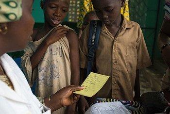 Une infirmière donne aux enfants leur carte de vaccination après avoir reçu la vaccination contre la rougeole et la poliomyélite, ainsi qu'un supplément de vitamine A au Centre de santé de Madina à Guéckédou, en Guinée.