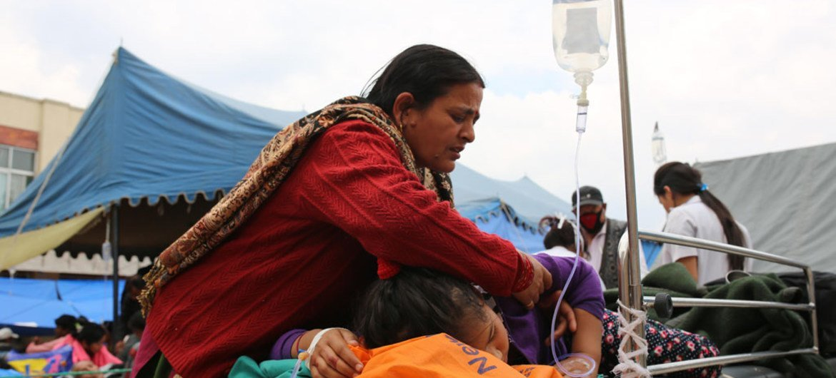 A mother tends to her daughter, injured in Nepal's recent earthquake, at the Tribhuvan University Teaching Hospital in Kathmandu. Most patients have been moved outside, as the country experiences continuing aftershocks.