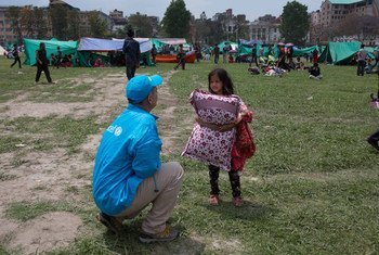 A UNICEF worker speaks to a child seeking temporary shelter at a vacant field next to Nepal's army headquarters in Kathmandu following Nepal's massive earthquake.