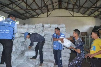 UNHCR staff collect plastic sheeting from a warehouse before it is distributed to people in eastern Nepal affected by the devastating earthquake.