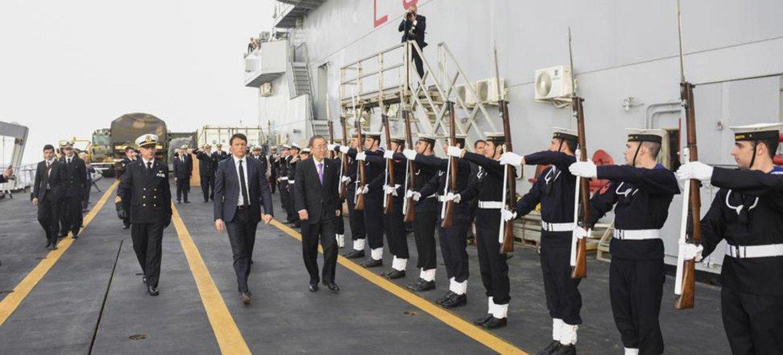 Secretary-General Ban Ki-moon (walking, right) on board the Italian naval vessel, San Giusto, in Sicily.