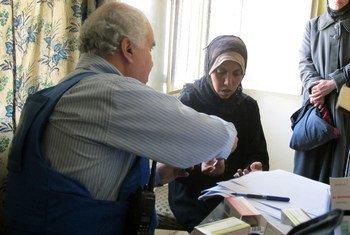 一位妇女接受近东救济工程处医疗人员的诊断。近东救济工程处图片