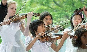 Children performing a violin composition during a special ceremony to commemorate the return of the Peace Bell to its original location in the Japanese Garden, at UN headquarters.