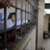 Un employé du HCR surveille la situation de Rohingya dans un centre de détention de migrants en Thaïlande. Photo HCR/V. Tan